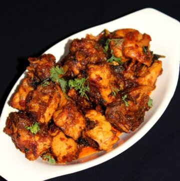 chicken fry in a bowl garnished with coriander leaves