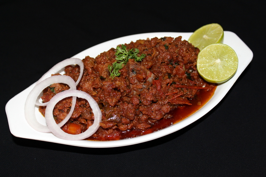 mutton keema in a bowl with garnished onion rings