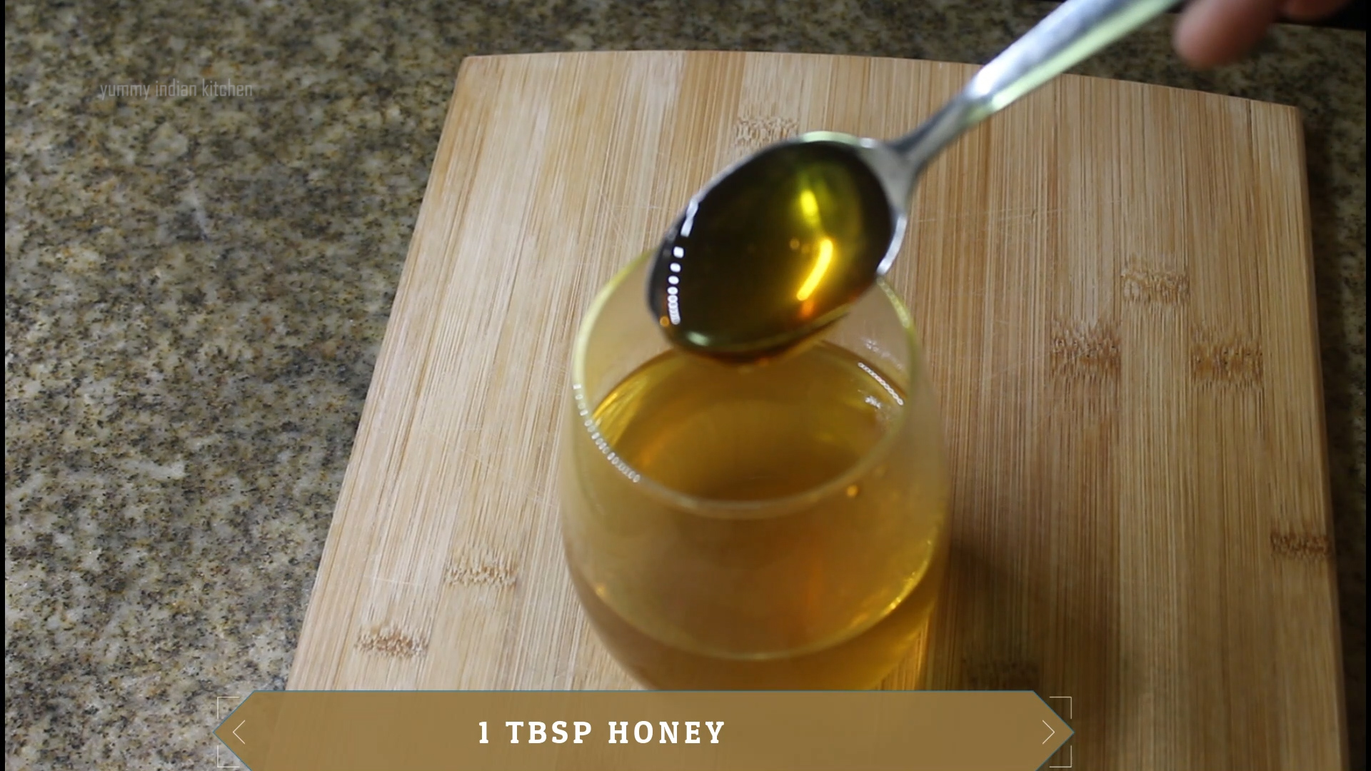 adding a teaspoon of honey to the water in glass