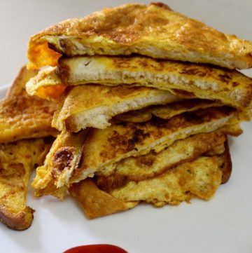 cooked bread omelette plated by slicing into two halves