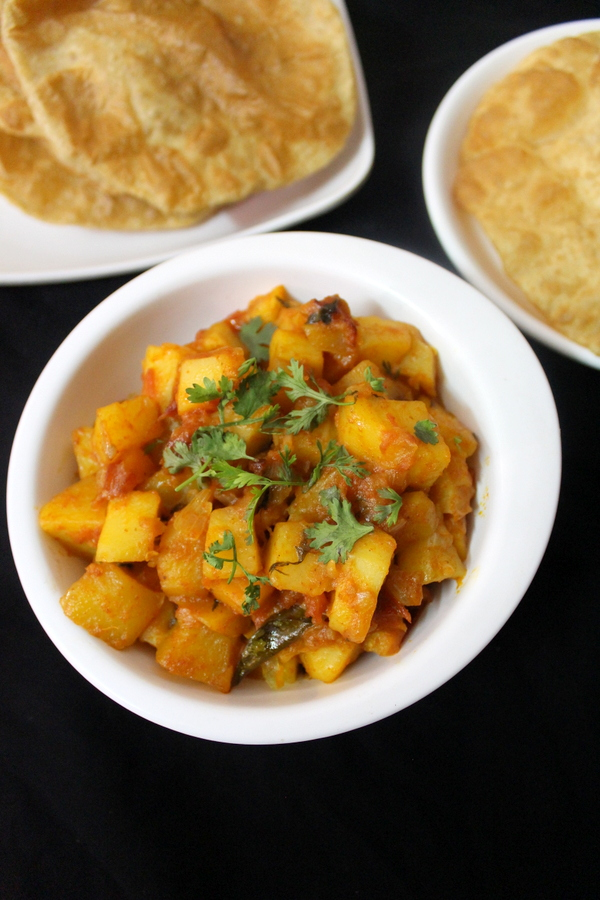 aloo curry recipe and poori placed beside