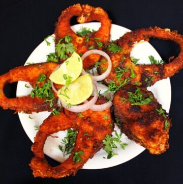 fish fry masala on a plate with onions and lemon