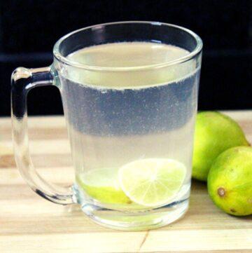 lemon water in a glass with lemon slices inside