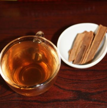 cinnamon water in a cup with cinnamon sticks in a small bowl