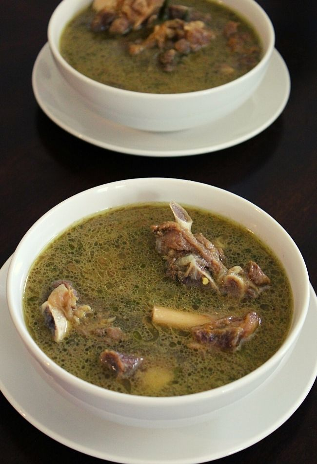 mutton soup placed in two serving bowls with mutton on the soup