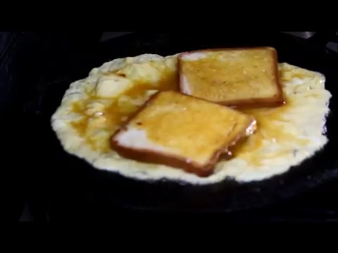 two bread slices on an omelette sandwich cooking well
