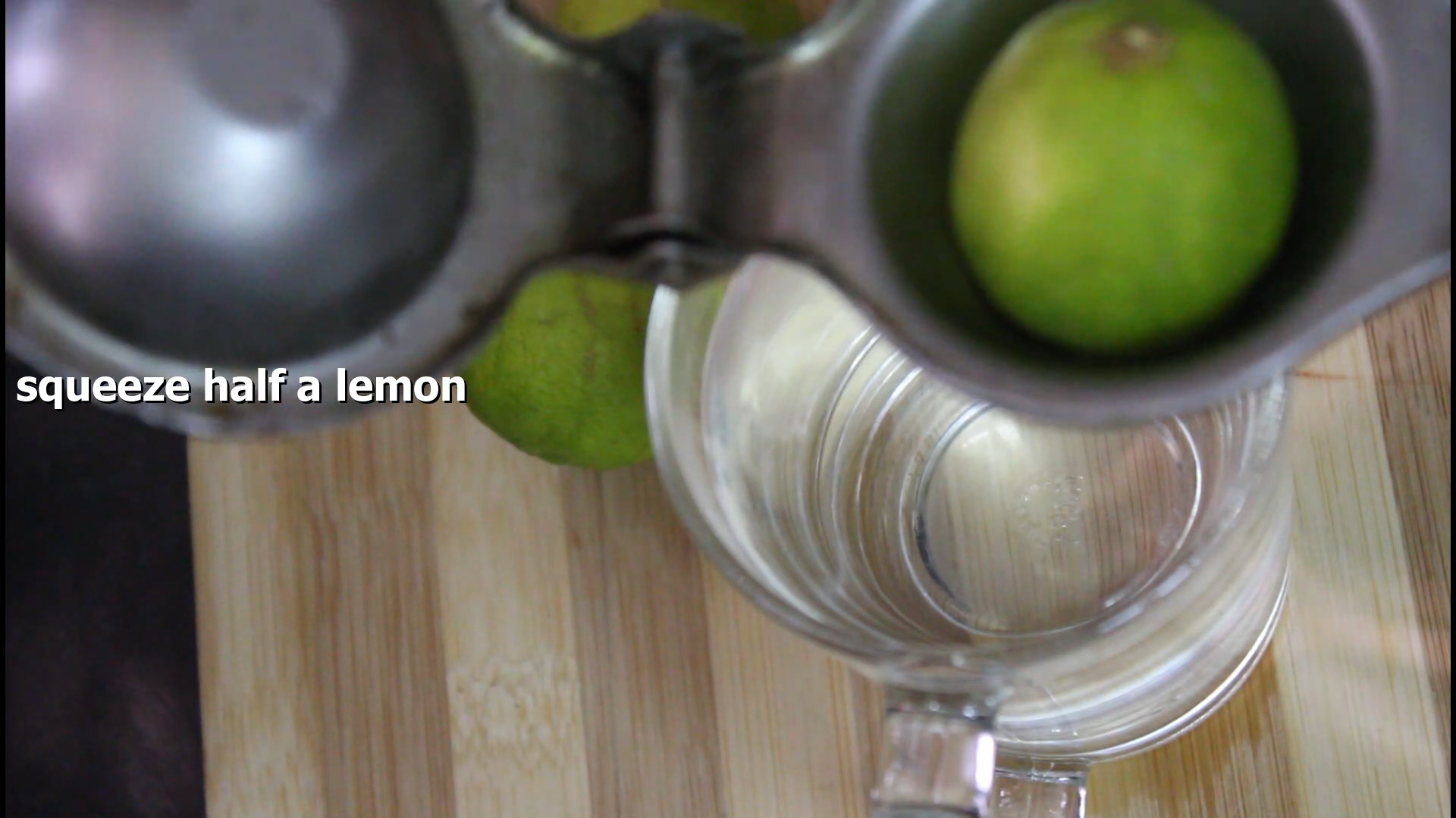squeezing out lemon juice into the glass using a lemon squeezer