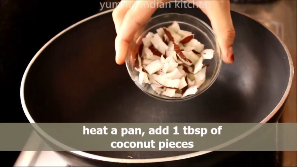Adding coconut pieces into the pan
