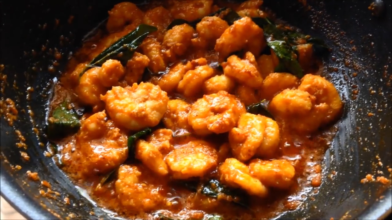 cooked prawns fry with gravy appearing at the sides inside the wok