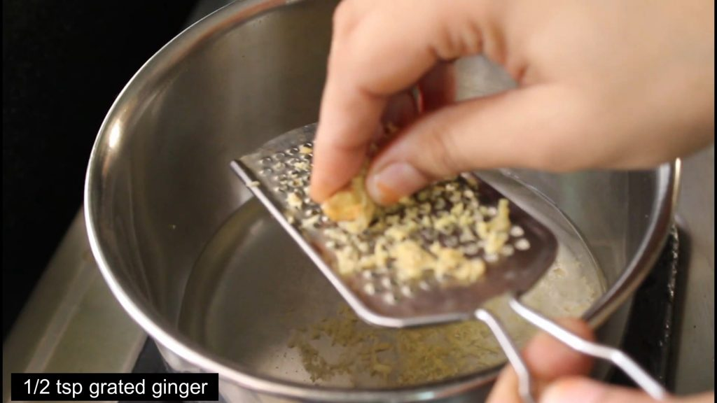 grating ginger into the water in the pan