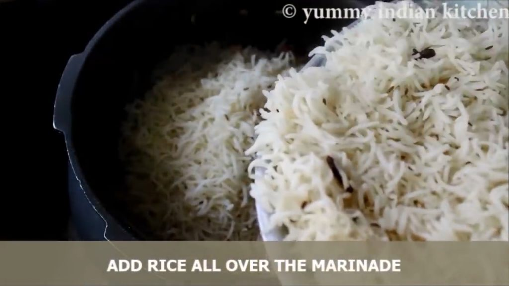adding the biryani rice that has been strained and spread it evenly.