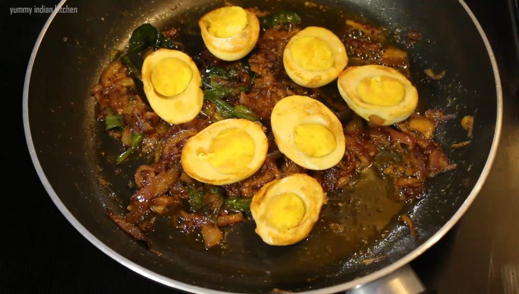 adding the eggs to fry in the pan to cook with masala