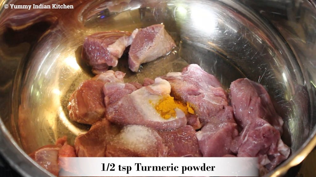 adding the mutton pieces into the cooker along with salt and turmeric