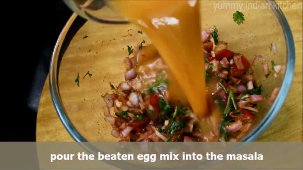 Taking the beaten egg mixture and adding it into the onion tomato masala mixture