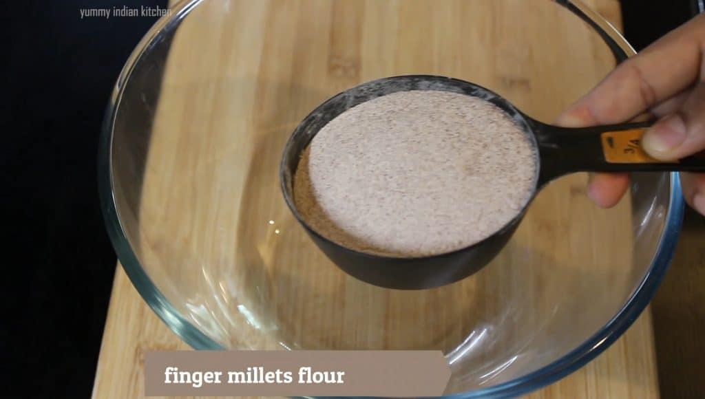 adding ragi flour to a mixing bowl