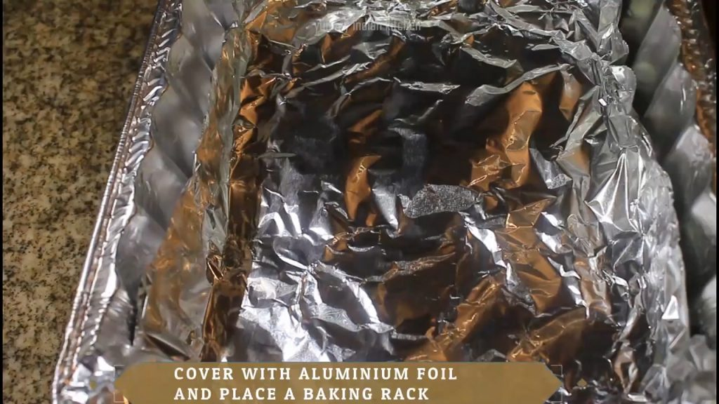 Taking a baking tray and cover it with an aluminium foil