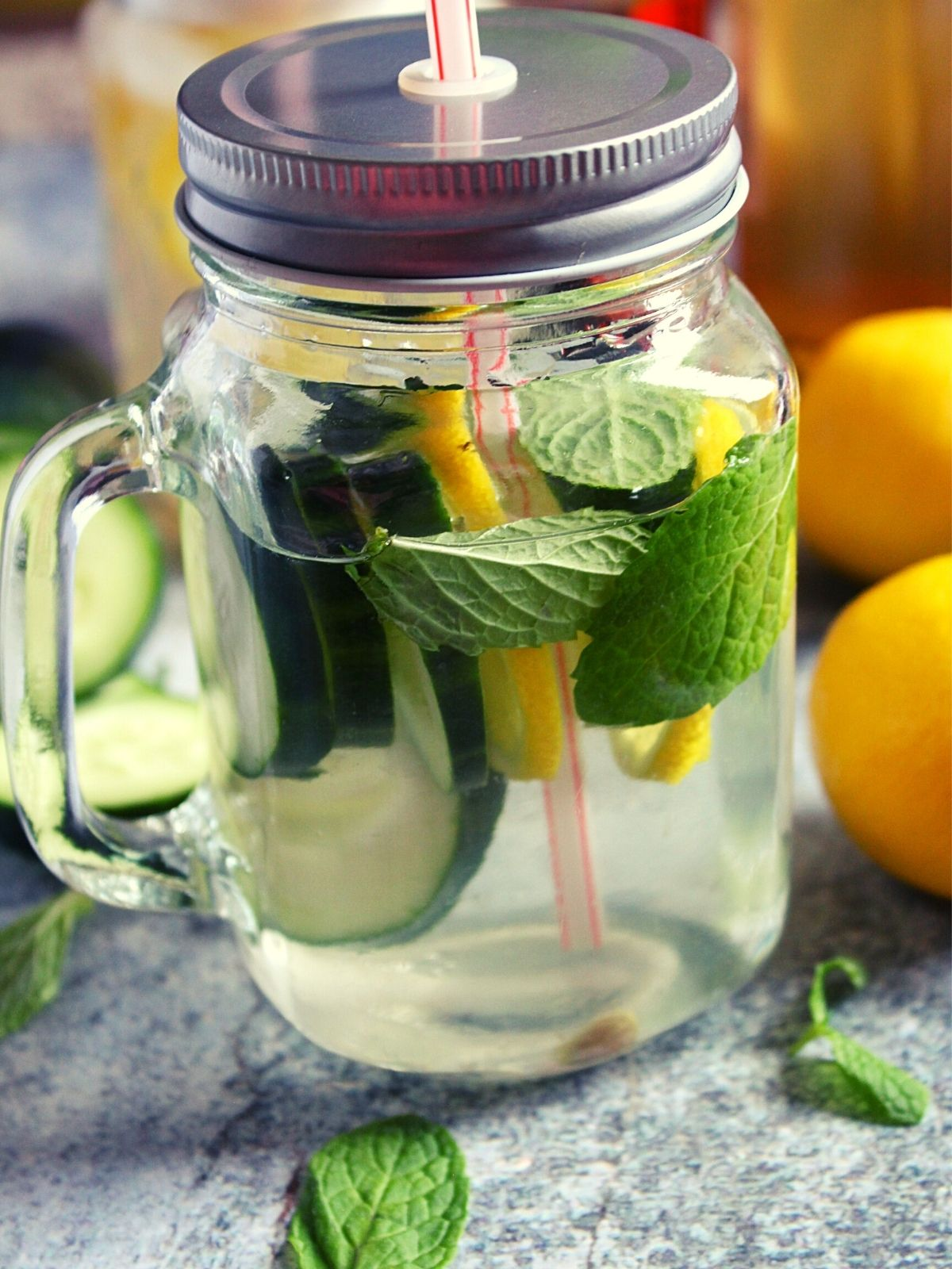 lemon cucumber infused water in a glass jar with a lid and straw