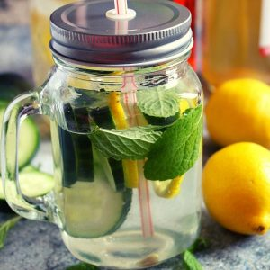 lemon cucumber slices with mint leaves infused water in a jar with a lid
