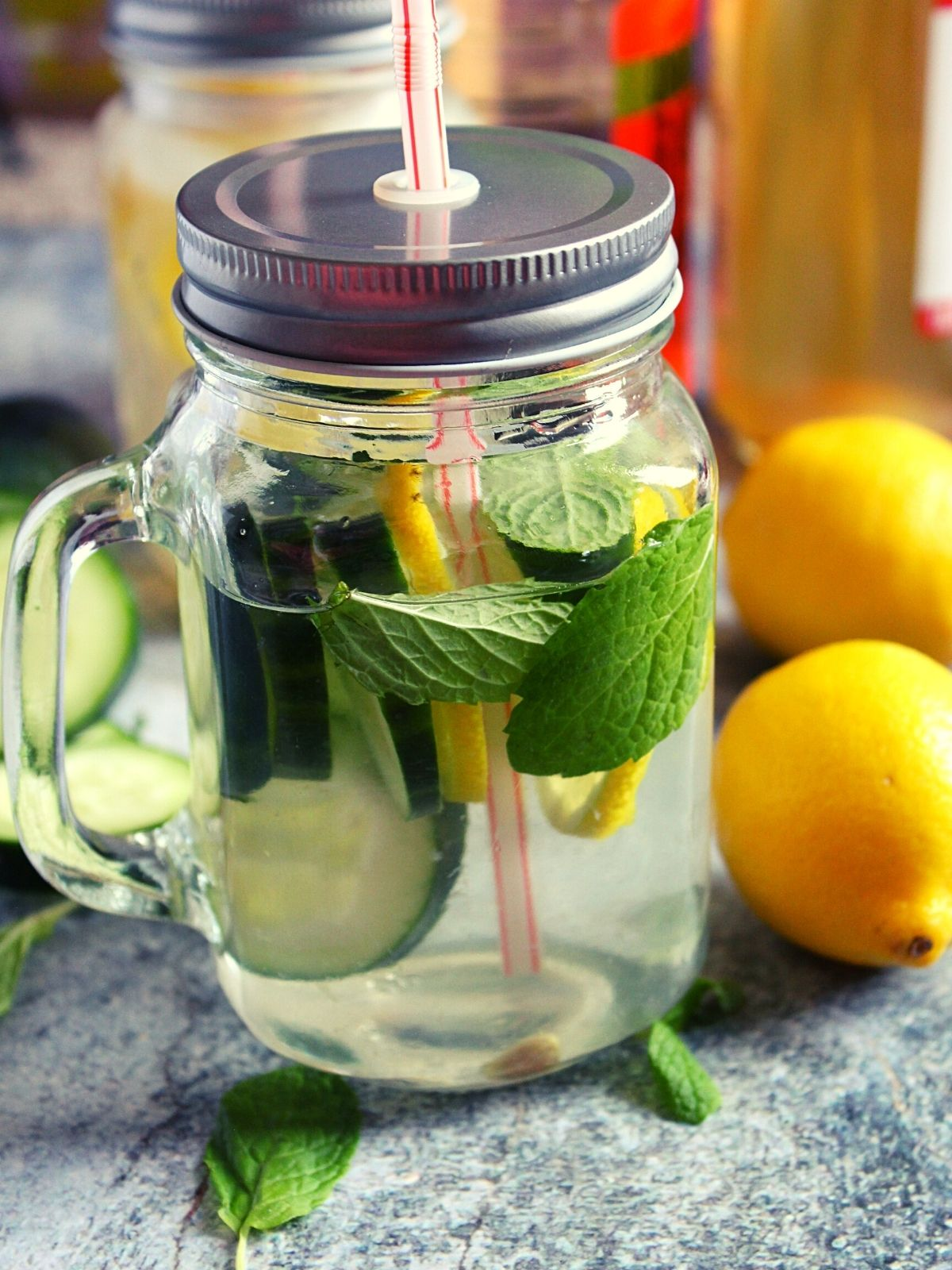 lemon cucumber slices with mint leaves infused in water in a jar with lid
