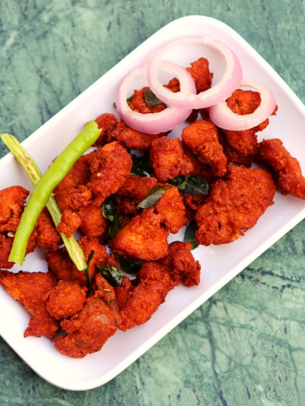 deep fried pakora served on a plate with onions and chilli topping