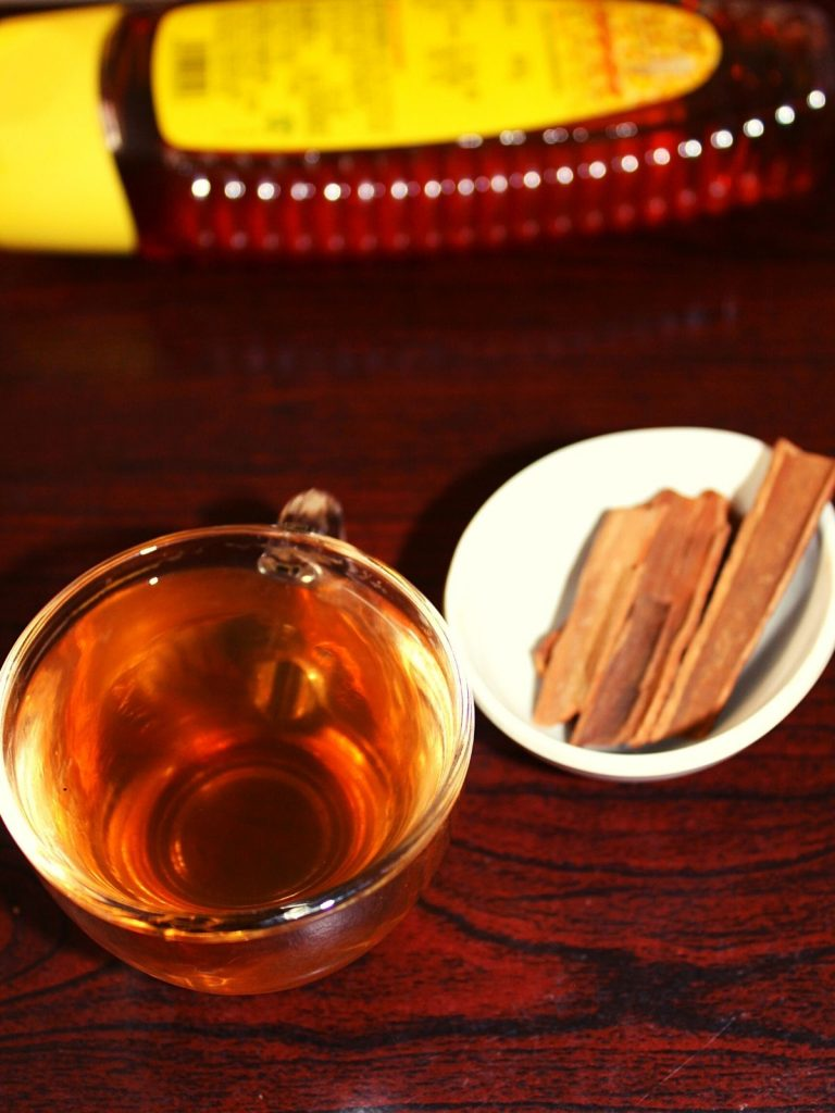cinnamon drink in small cup with cinnamon sticks placed beside in a small bowl