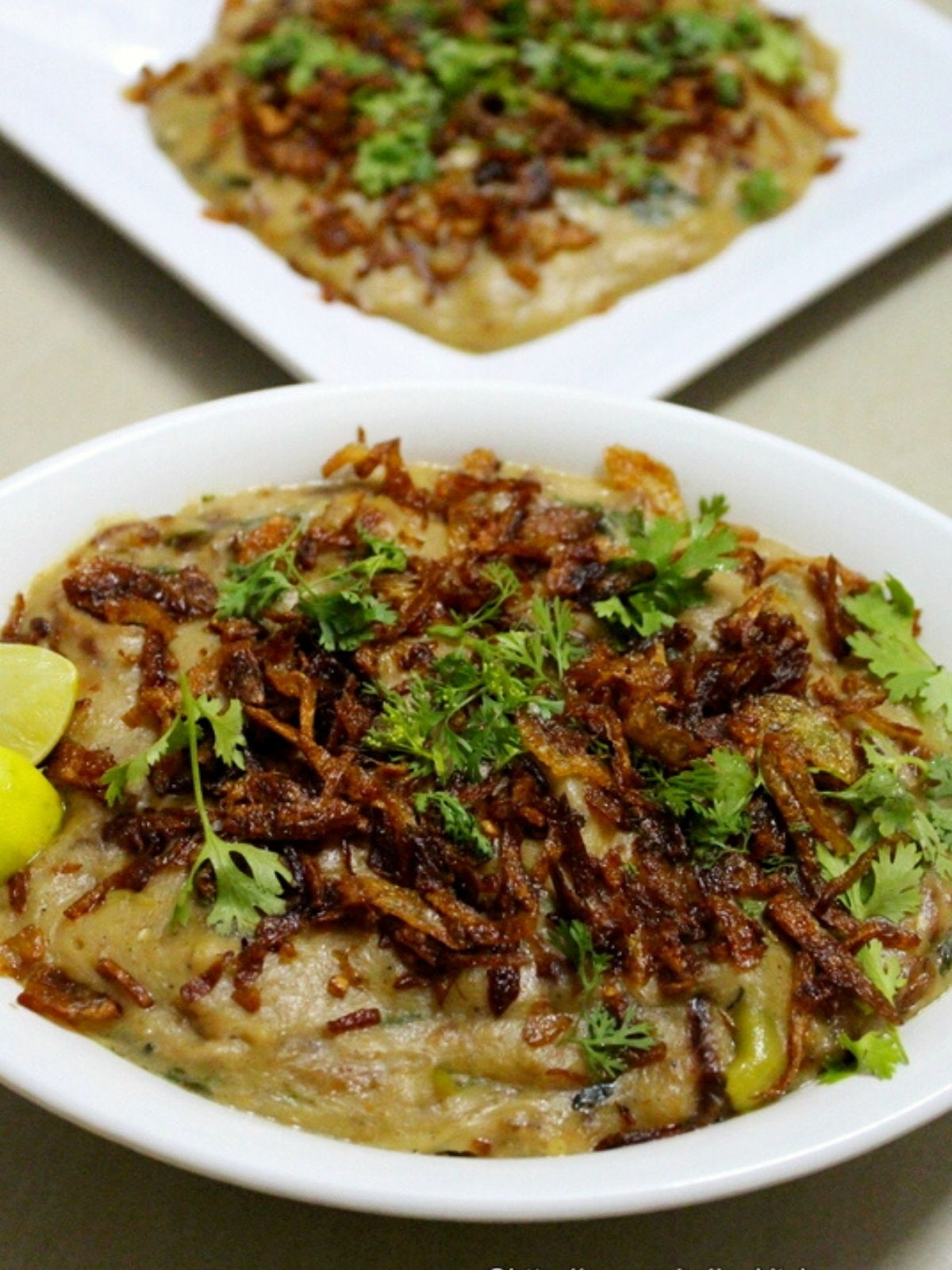 haleem recipe served in a bowl with fried onions as topping