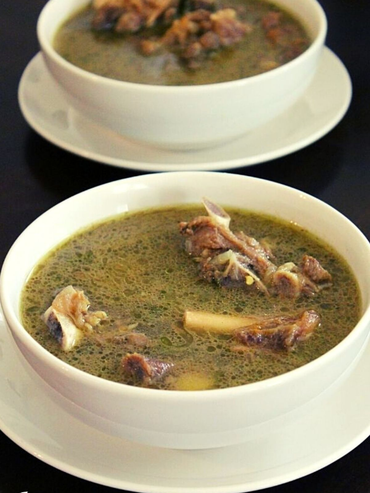 mutton soup placed in two serving bowls with cooked mutton pieces on the soup