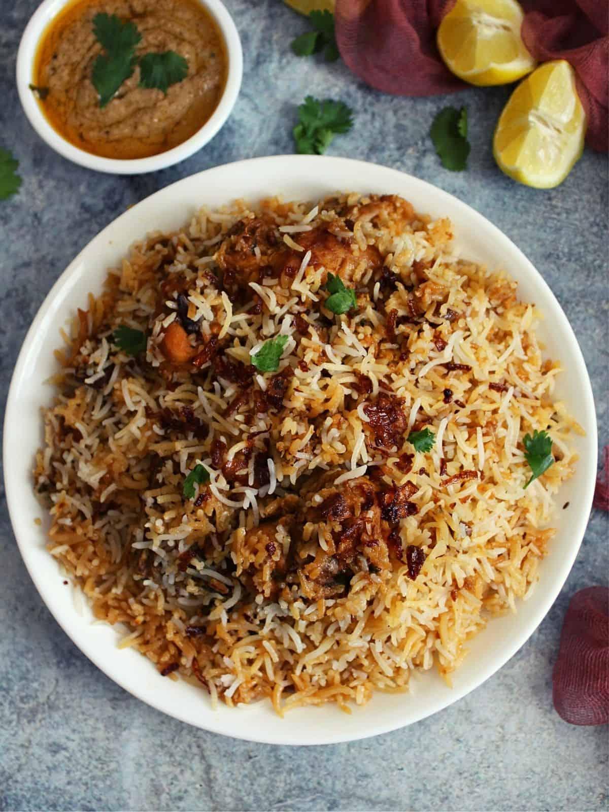 chicken dum biryani hyderabadi style on a plate with mirchi ka salan