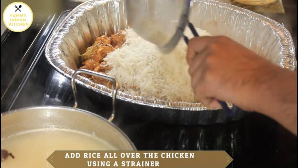 spreading the rice to make chicken dum biryani in oven