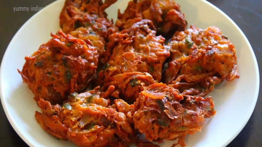 placing the fried kanda bhaji on a tissue paper
