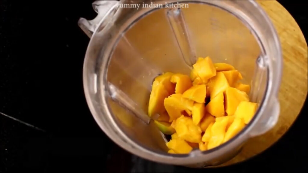 Adding the cubes of mango into the jar