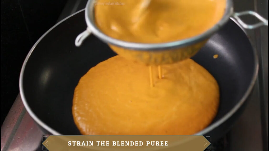 straining the blended tomato cashew nut puree into the pan