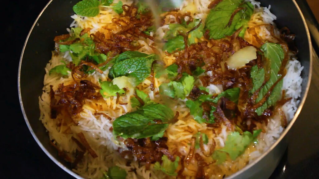 Topping pakistani biryani with some mint leaves, coriander leaves and some deep-fried onions, ghee and oil