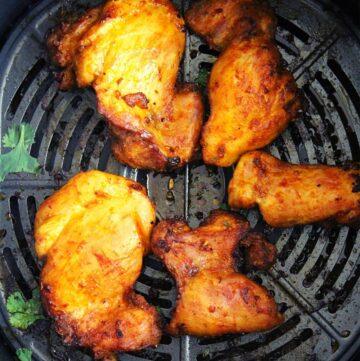 air fryer boneless chicken thighs showing in an air fryer