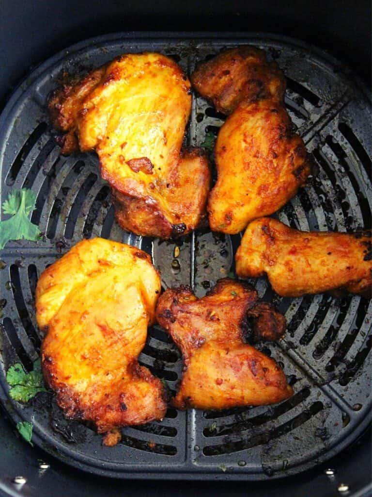 air fryer boneless chicken thighs showing in air fryer