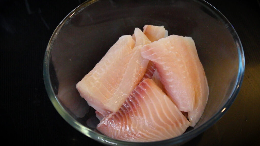 Adding fish pieces to a mixing bowl.