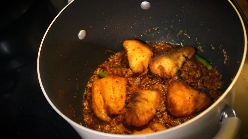 Placing the fried fish pieces over the curry base