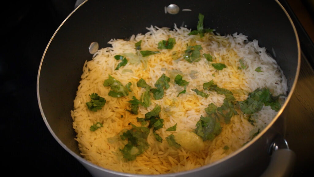 adding toppings of oil, food color and ghee on fish biryani