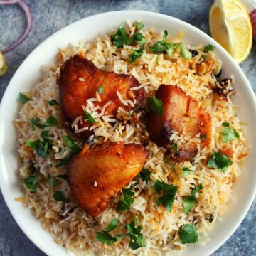 fish biryani with fried fish pieces on a plate