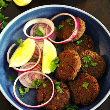 shami kabab in a bowl with onion rings and lemon