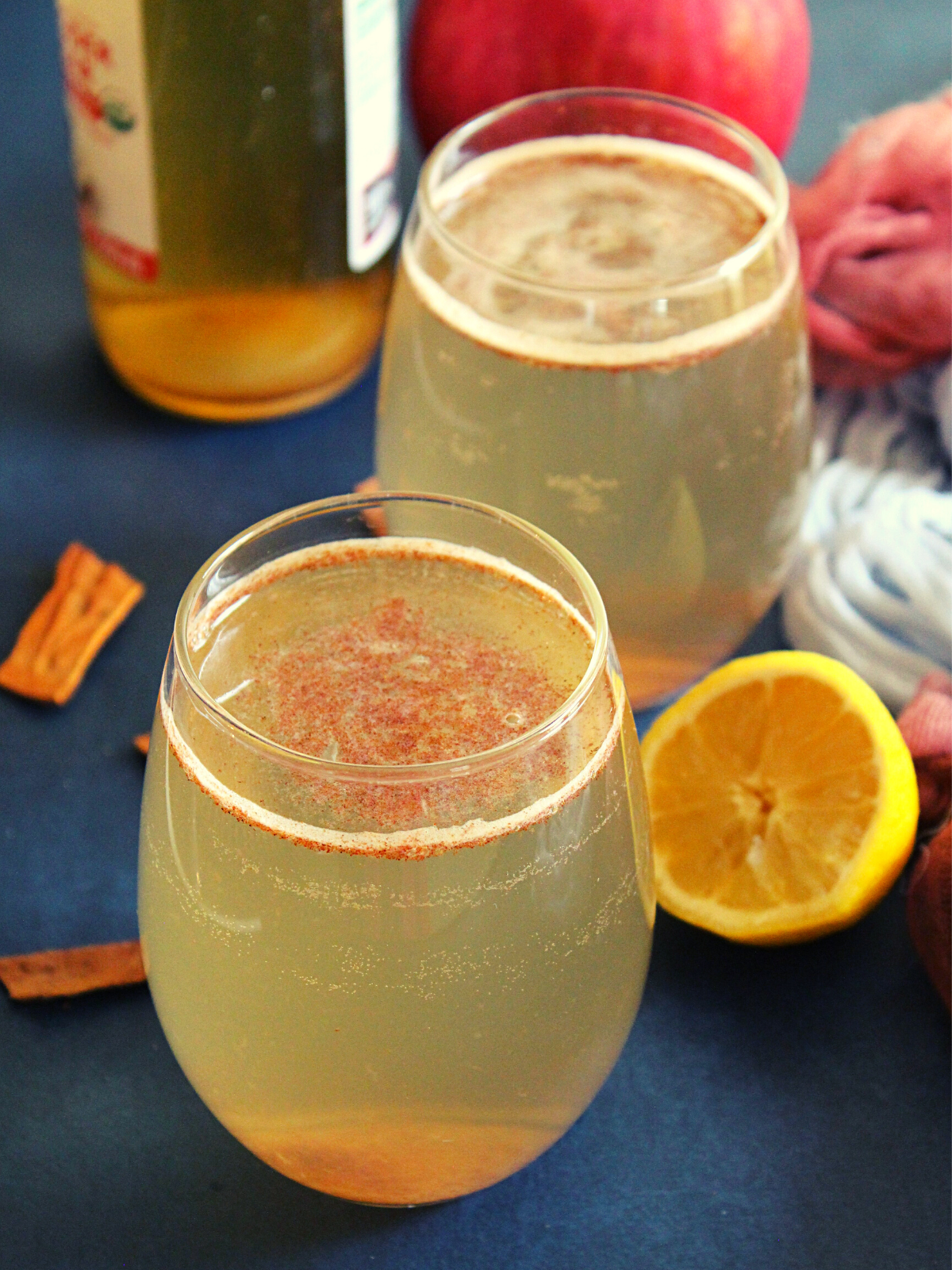 apple cider vinegar and honey drink with cinnamon is served in a glass with lemon