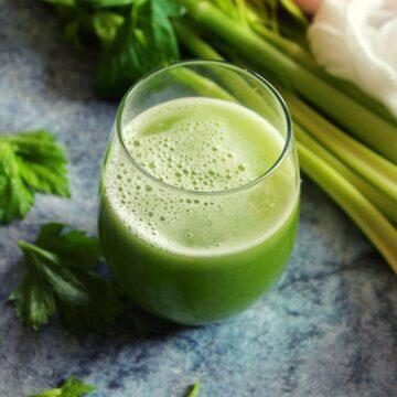 celery juice served in glass with celery stalks beside