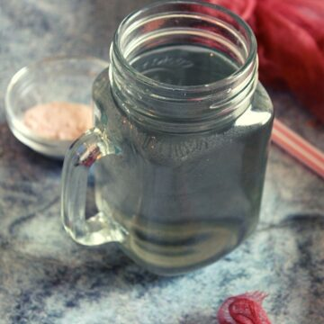 salt water in small jar with pink salt placed beside